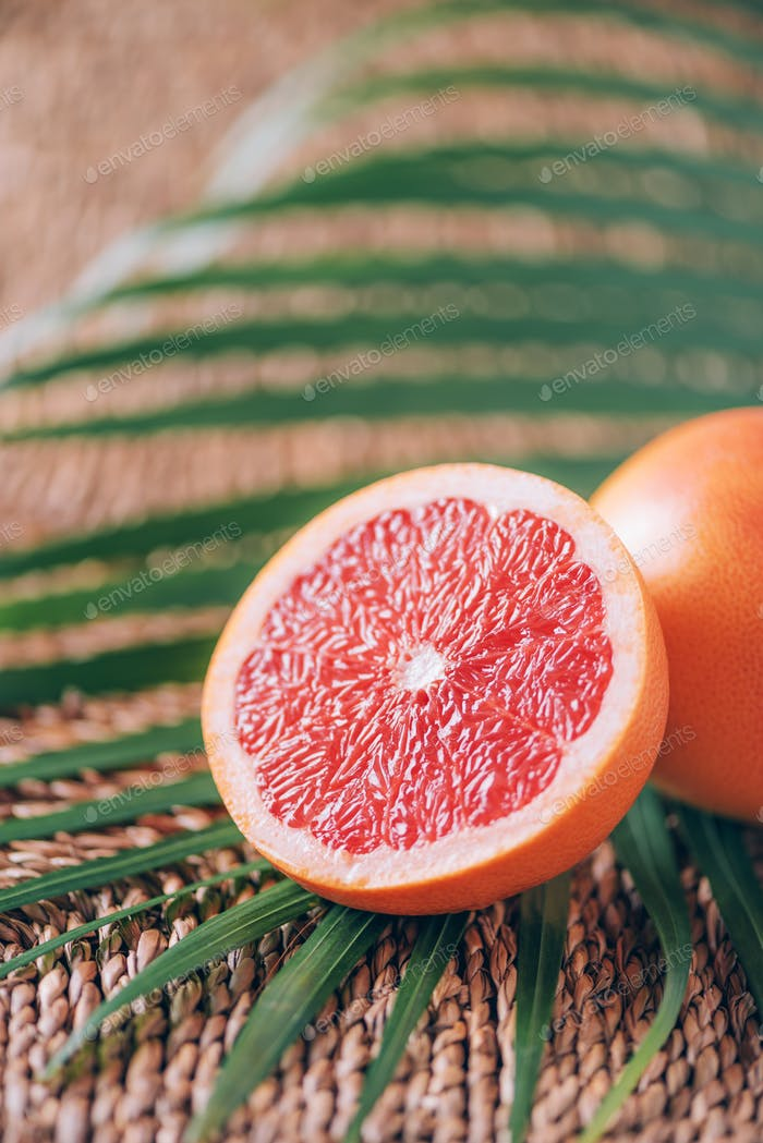Fresh red grapefruit with palm leaves on rattan background. Copy space. Creative design banner