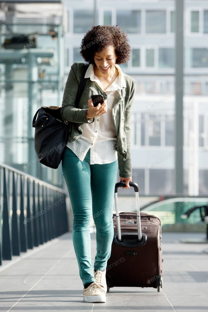 Ganzkörper ältere Frau zu Fuß am Bahnhof mit Koffer und Handy