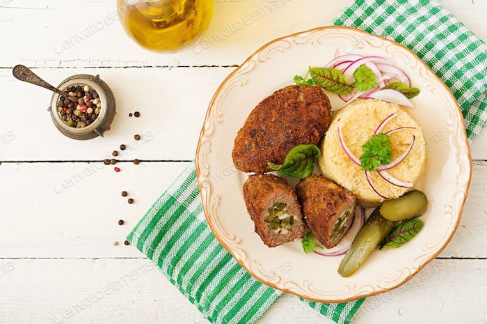 Zrazy Schnitzel mit Hackfleisch mit eingelegten Gurken und Eiern und Garnierung von Bulgur