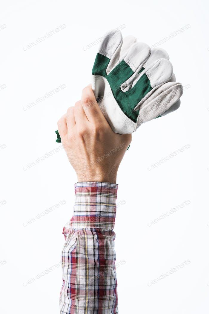 Hand holding gardening gloves