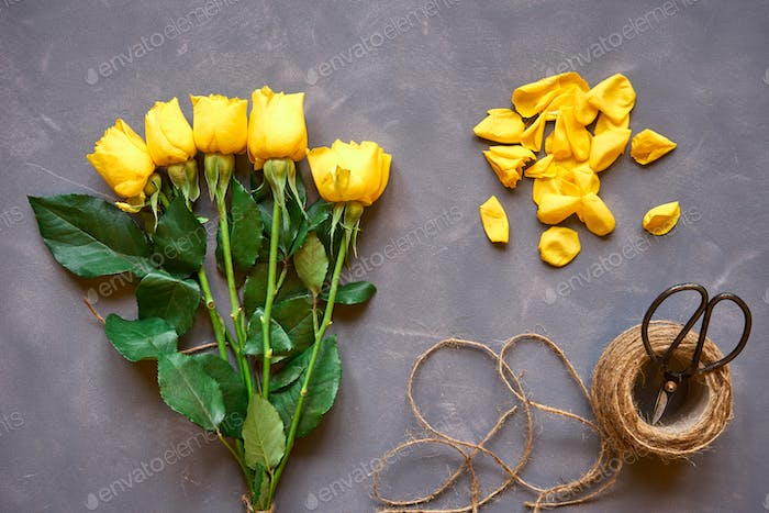 Yellow roses bouquet and accessories on   grey background