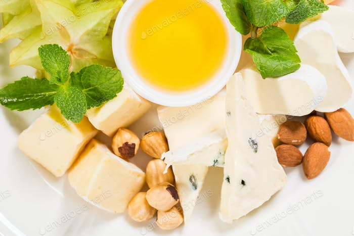 Delicious cheese platter with nuts and honey.