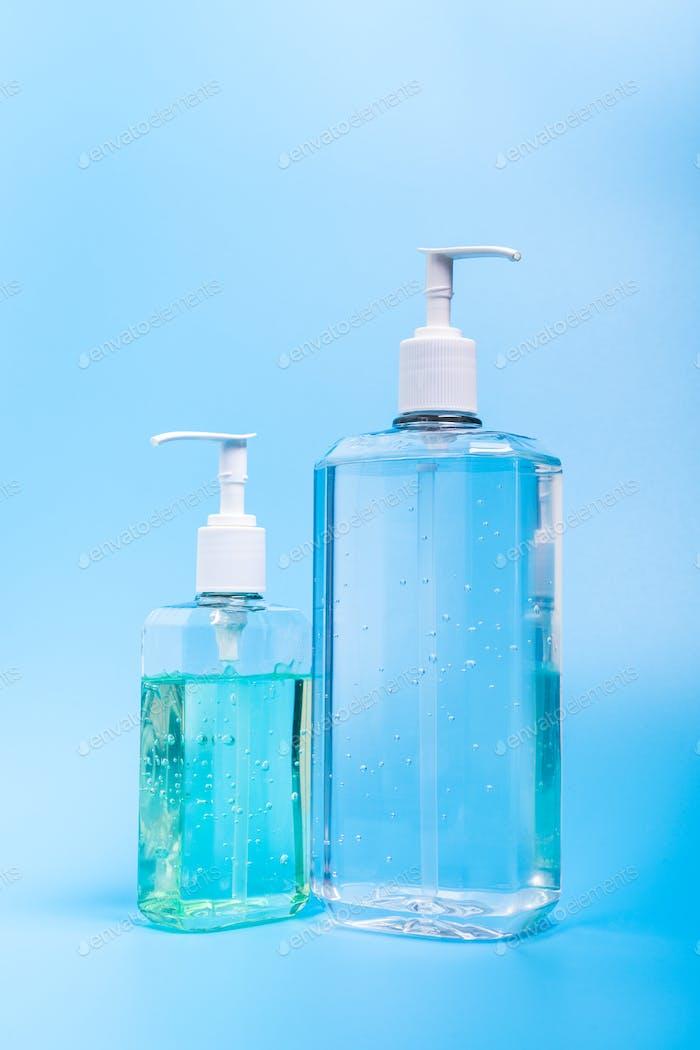 Zwei-Hand-Desinfektionsmittel in Plastikflasche auf blauem Hintergrund