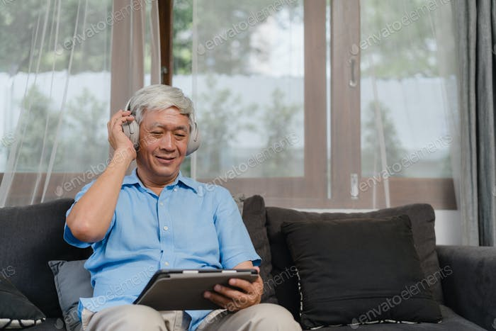 Asian older male happy wear headphone using tablet listening podcast while lying on sofa.