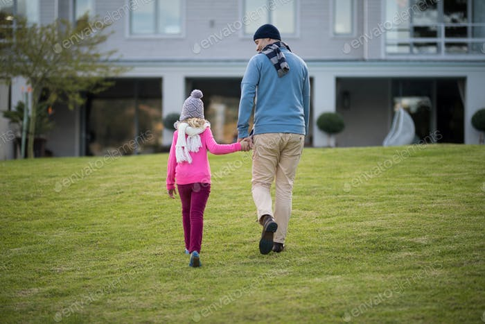 Father and daughter holding hands and walking in the garden