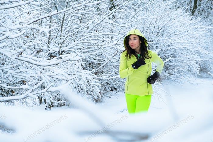 Middle aged woman in green sportswear running in winter snow park. Happy fit middle aged woman trail