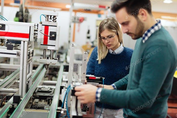 Zwei junge, gut aussehende Ingenieure arbeiten an Elektronikkomponenten