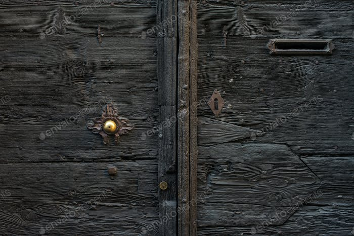 Old medieval italian wooden door with metal handle and a mail slot.