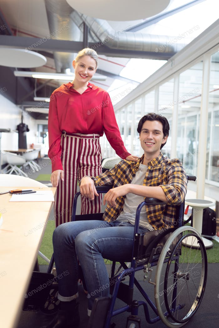 Front view of Caucasian male and female fashion designers looking at camera at desk in office