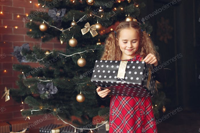 Little girl standing near christmas tree with present