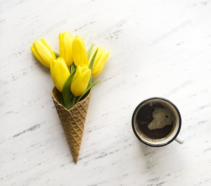 Tulips in ice cream cone on marble background