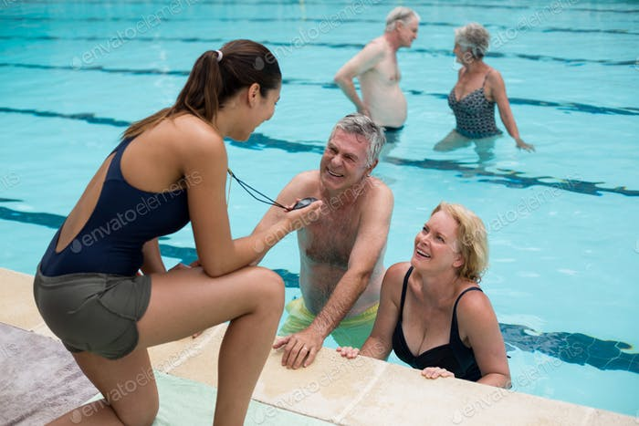Trainer discussing timing with senior swimmers at poolside