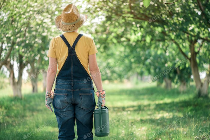 Female farmer with watering can in organic orchard