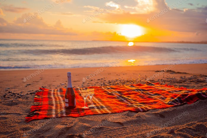 Having a picnic on the beach at sunset