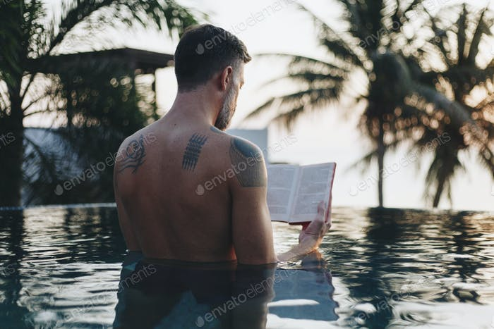 Man reading a book in the swimming pool