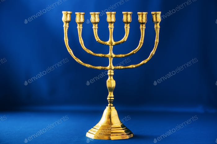 Golden hanukkah menorah on blue background. Jewish holiday banner with copy space. Ancient ritual