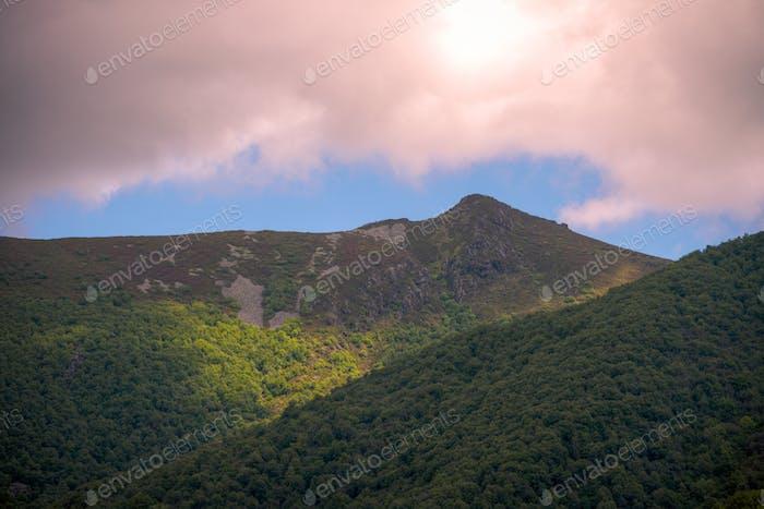 Ein Berg aus nackten Felsen entsteht aus einer bewaldeten Masse