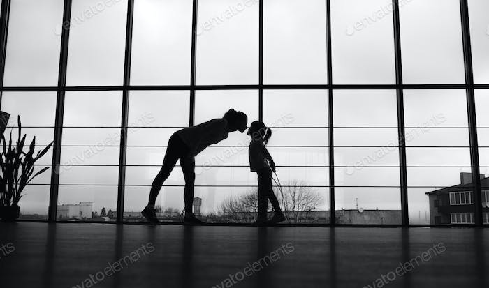 Silhouette of mother and daughter in the gym.Kiss