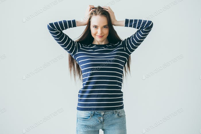 Europäische Frau mit dunklen und langen Haaren, die Hände in ihren Haaren vor einem grauen Hintergrund halten.