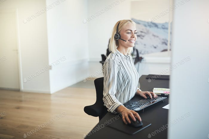 Smiling businesswoman working at her desk and wearing a headset