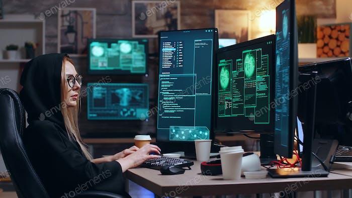 Female hacker wearing a hoodie using a dangerous virus