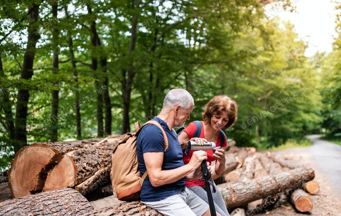 Senior tourist couple with flask on a walk in forest in nature, sitting.