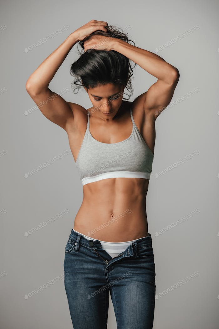 Woman in halter top holds hair with both hands