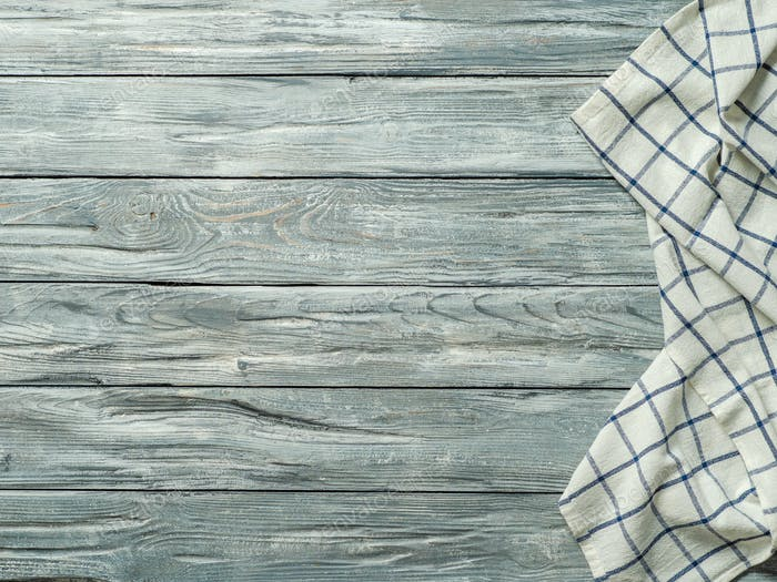 Gray wooden table with kitchen napkin, flat lay
