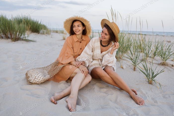 Fashion image of two pretty models sitting on the beach