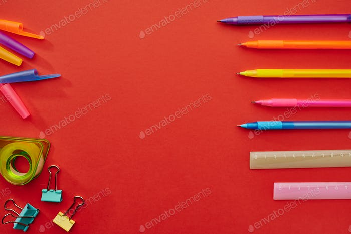 Pens, rulers and paper clips, red background