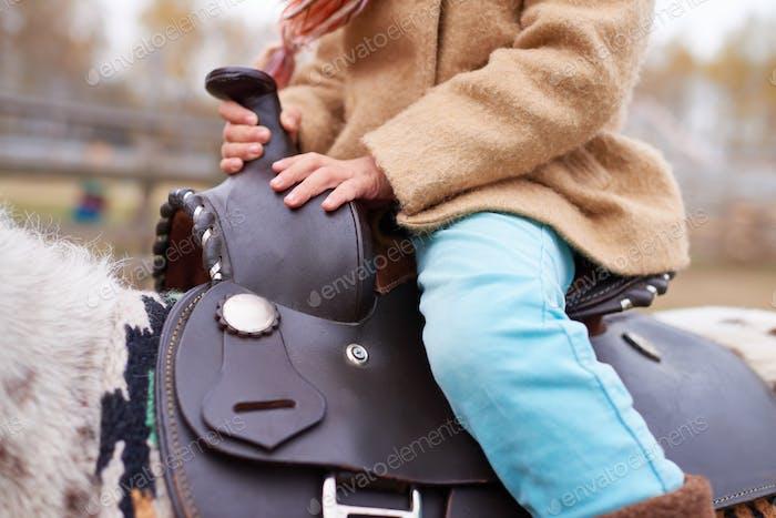 Unrecognizable Child Sitting On Horseback