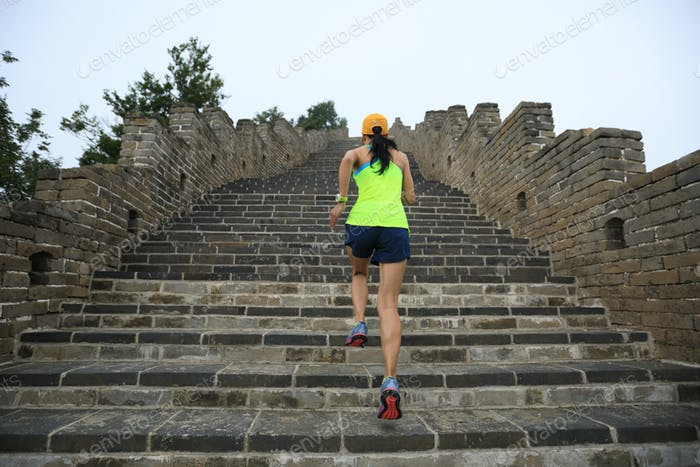 Woman running upstairs on great wall in China