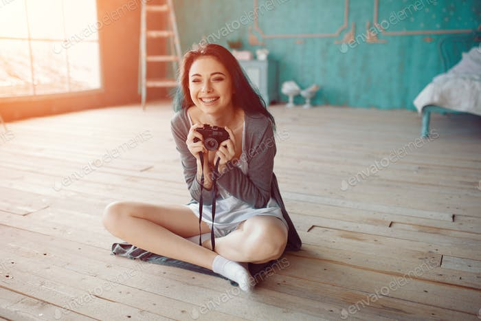 Portrait of pretty young girl taking picture on film camera