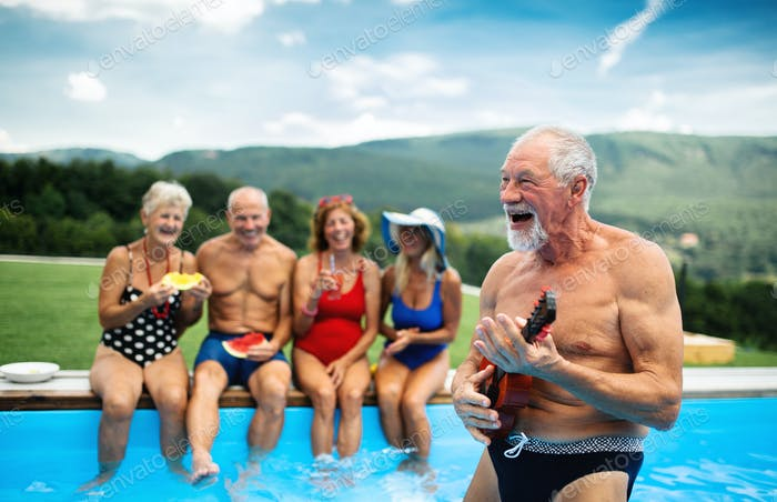 Group of cheerful seniors by swimming pool outdoors in backyard, party concept