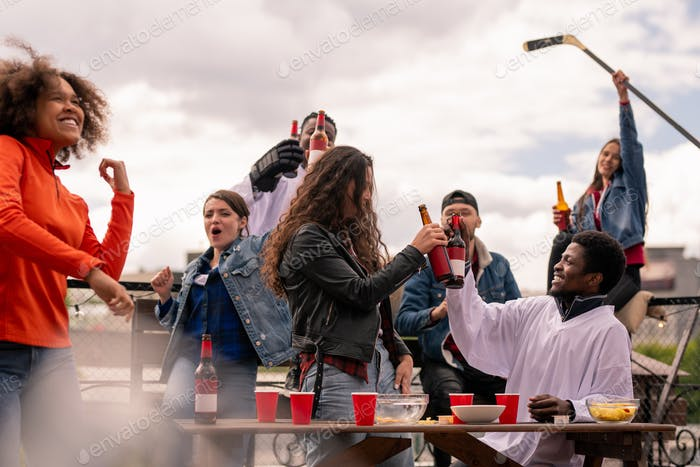Cheerful hockey fans clinking with beer while celebrating victory of their team