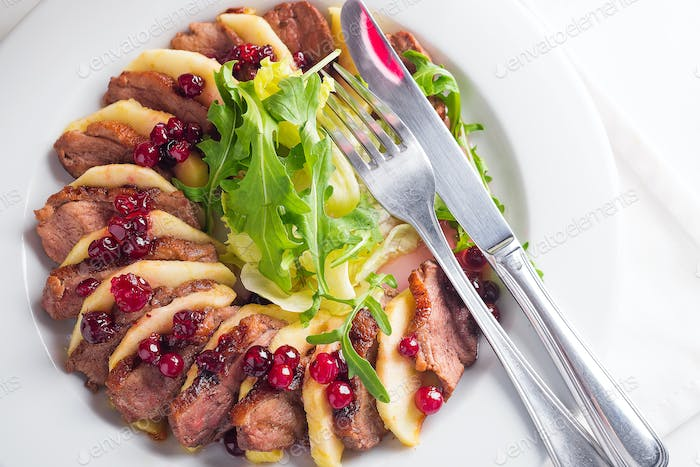 Salad with slices of duck breast with apples and salad under cowberry sauce