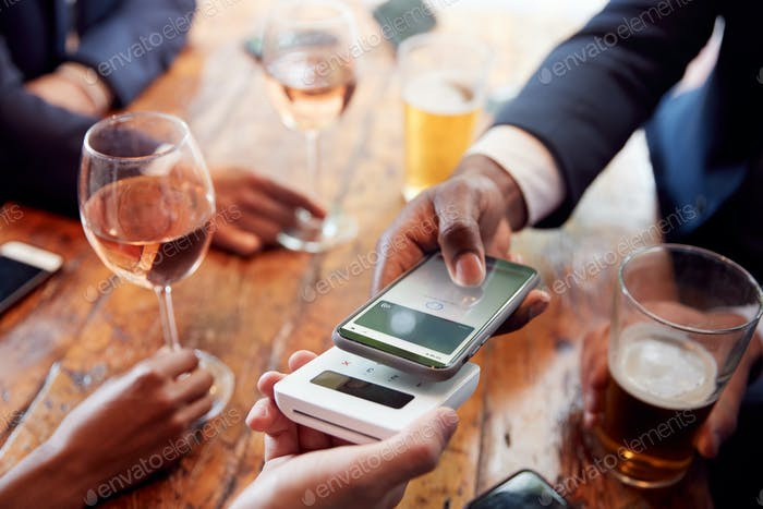 Close Up Of Businessman Paying For Round Of Drinks In Bar Using Contactless App On Mobile Phone