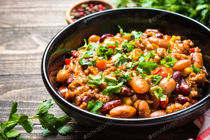 Chili con carne from meat and vegetables on wooden table top vie