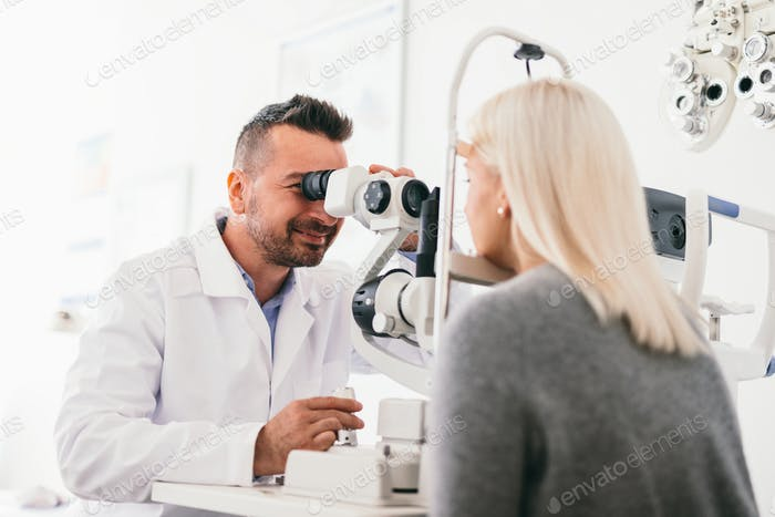 Optician examining woman's eyes with a machine.