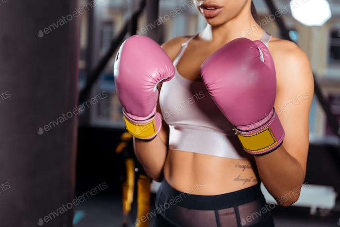 Partial view of strong girl in boxing gloves practicing boxing in gym