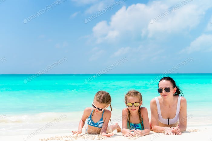 Portrait of young beautiful mother and her adorable little daughters at tropical beach