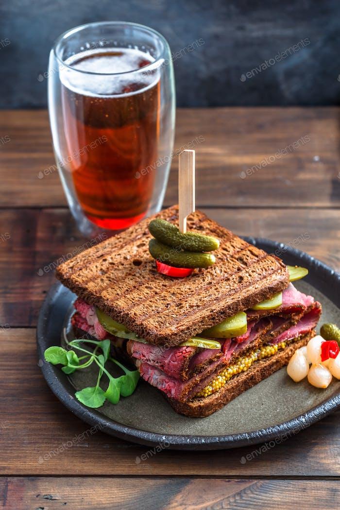 Köstliches riesiges Pastrami Sandwich mit Bier und Gurke