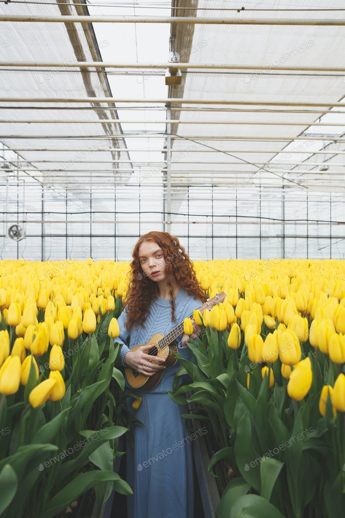 Girl with guitar in tulips