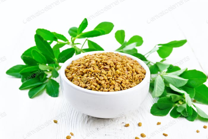Fenugreek with green leaves in bowl on white board
