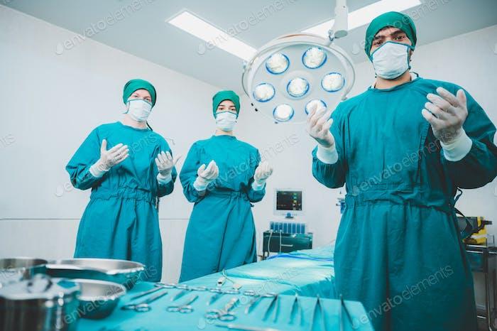 Porträt männlicher und weiblicher Chirurgen, die steriles Kleid mit Maske und Handschuhen tragen