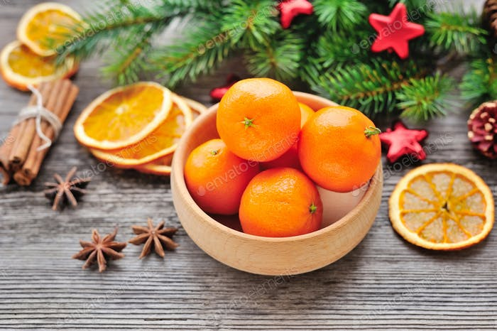Tangerines and Christmas tree branches on a wooden table