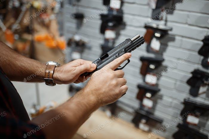 Mann wählt neue Pistole in Waffen-Shop