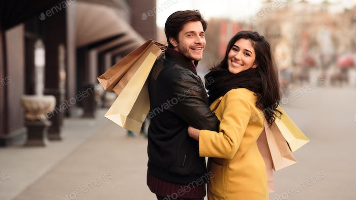 Loving couple walking after shopping in fashion shops