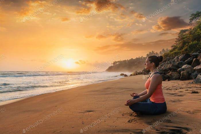 Woman doing yoga at beach - Padmasana lotus pose