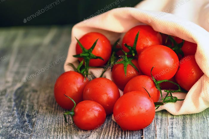 Red ripe tomatoes spill out of sack. Rustic view